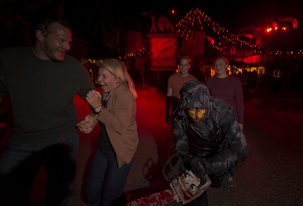 A woman in a brown sweater screams in fear as a zombie scares her at Howl-O-Scream at Busch Gardens Tampa