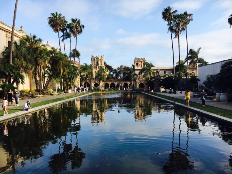 Reflecting pool at Balboa Park surrounded by museum architecture, palm trees, and a clear blue sky.