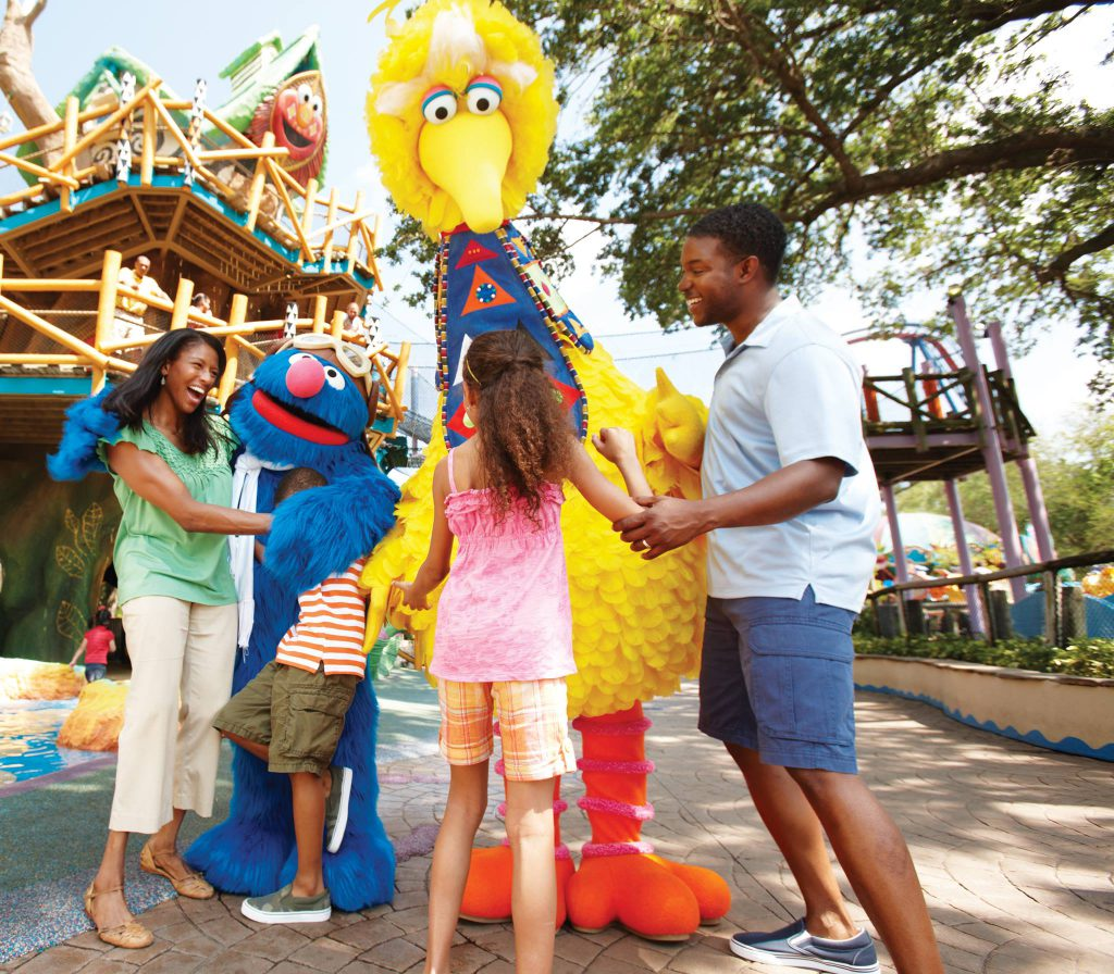 Big Bird and Grover from Sesame Street stand with a family (mom, dad, daughter, and son) during one of the Busch Gardens Tampa events.