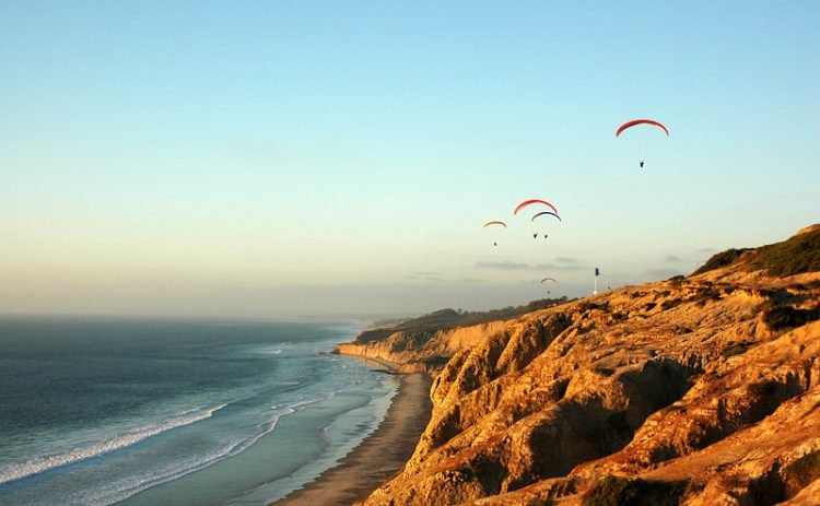 Hanggliders soar above the cliffs and ocean at Torrey Pines Nature Reserve in San Diego