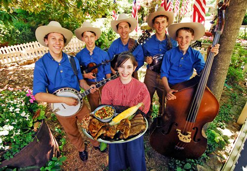 A western band dressed in blue shirts surround a woman holding a BBQ feast outside.