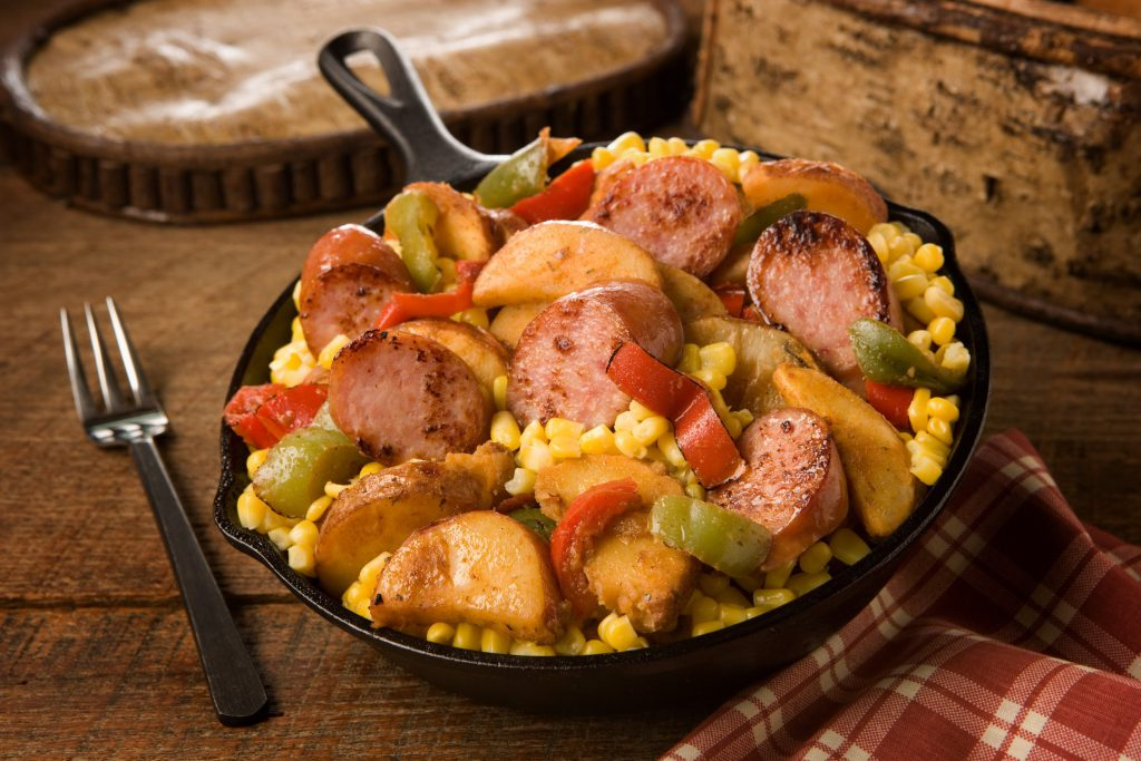 A massive cast iron skillet filled with sausage, potatoes, peppers, corn, and more.