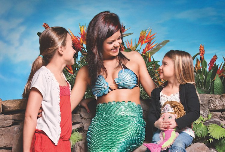 Two children, a toddler and early teenager, meet a mermaid character at an aquarium.