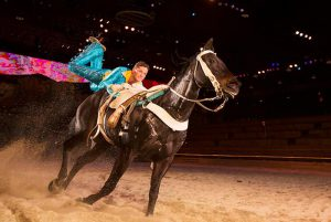 Man rides horse in indoor arena at Dolly Parton's Stampede in Pigeon Forge, TN