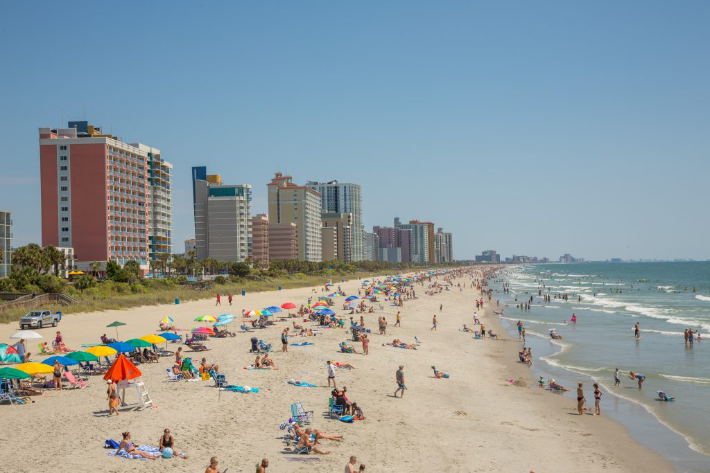 Free Things to Do in Myrtle Beach include going to the Beach - Beachgoers sit on the sand along Ocean Boulevard in Myrtle Beach