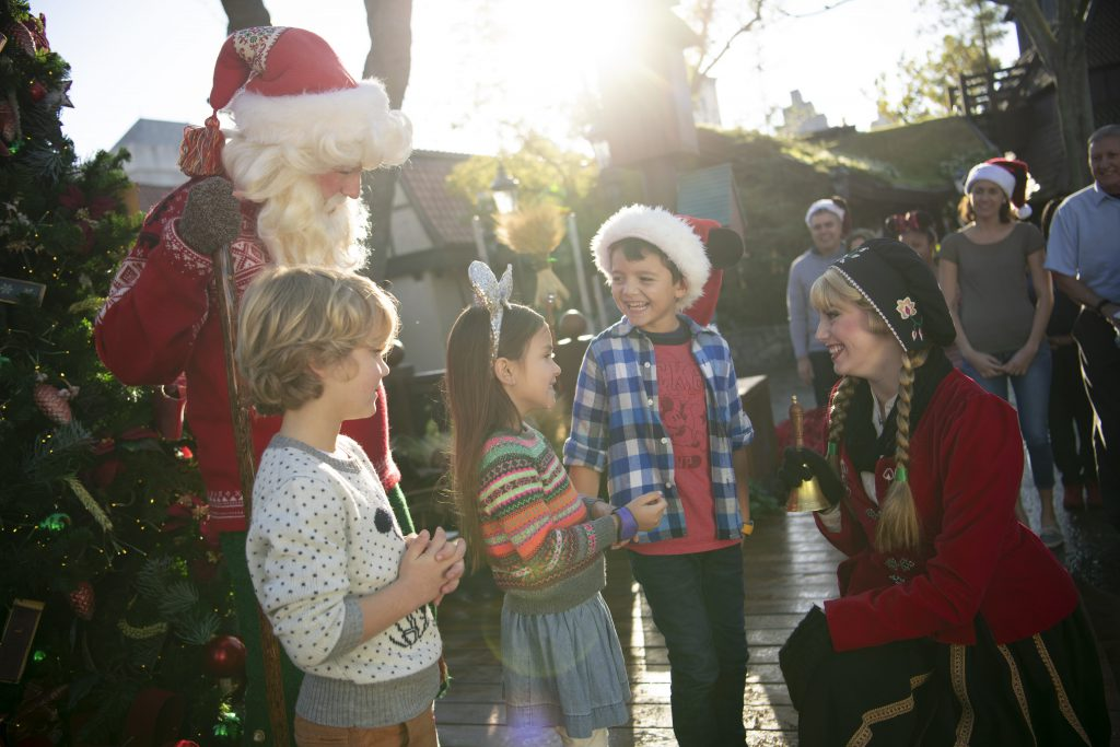 Children gather round for Christmas celebrations with team members dressed up in Christmas attire at Disney World