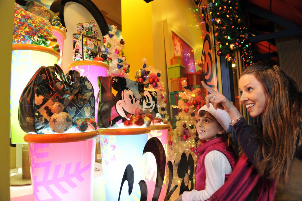 Mom and daughter shopping for Mickey Mouse accessories at Disney Springs