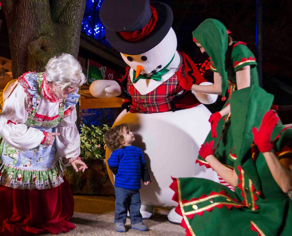 A little boy in a blue shirt looks up at Mrs. Claus, a snowman, and Christmas elves