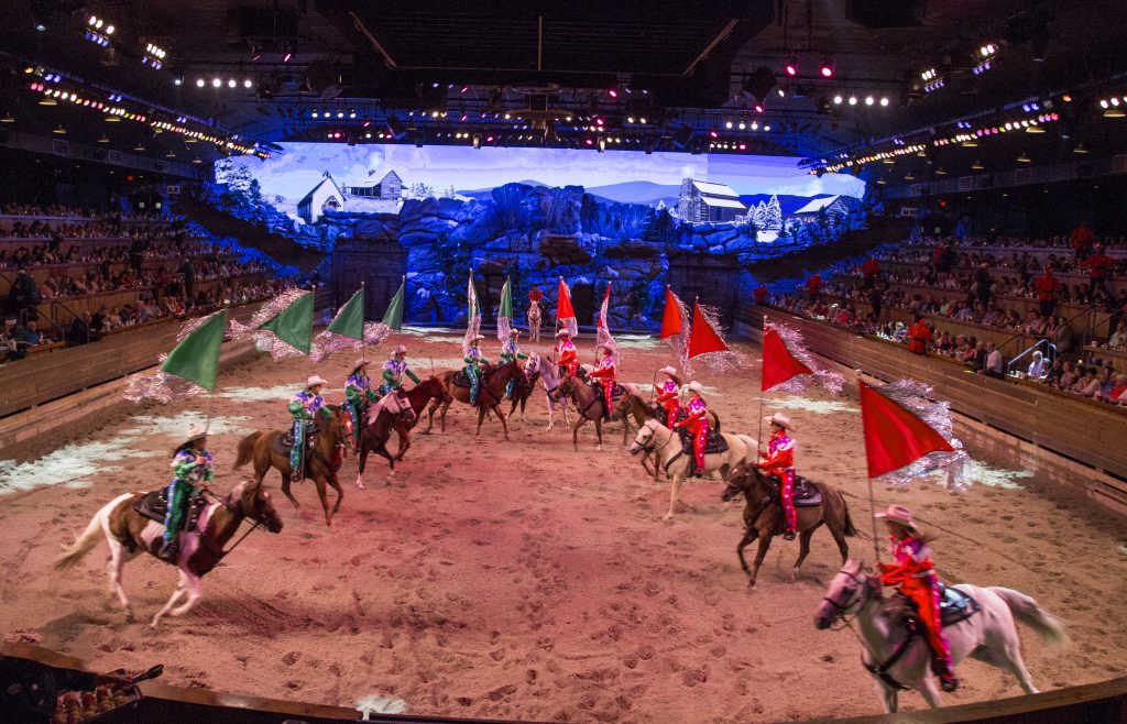 Dolly Parton's Stampede Christmas show features horse riders wearing either green or red costumes.