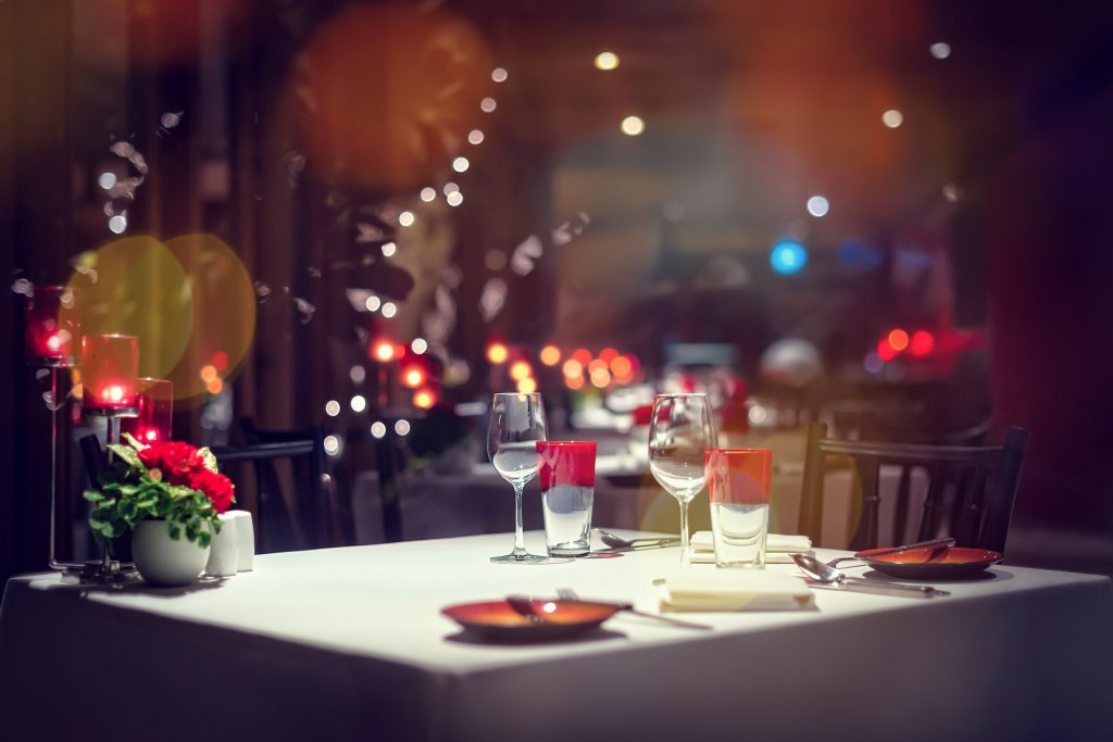 A table with a white tablecloth and red holiday decor and wine glasses in a dimly lit restaurant