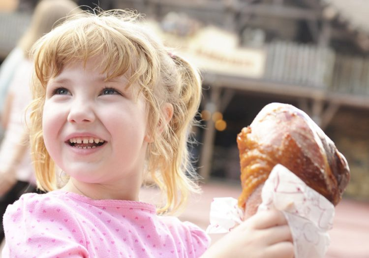 A little girl with blond hair and a pink shirt eats a giant turkey leg during a Disney World Thanksgiving