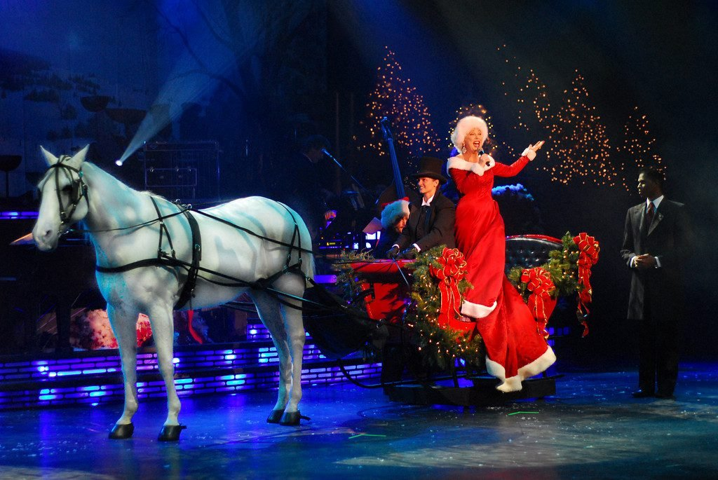A woman in a Mrs. Claus outfit rides a horse-drawn carriage decked out in Christmas wreaths on stage for a Christmas show.