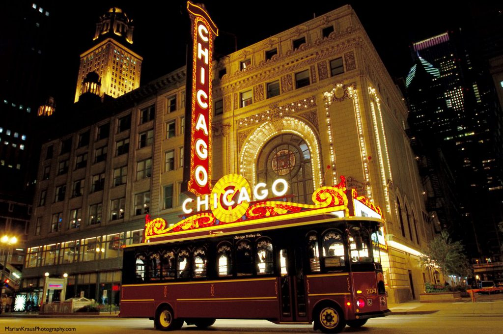 The Chicago trolley rolls by the Chicago theatre at night