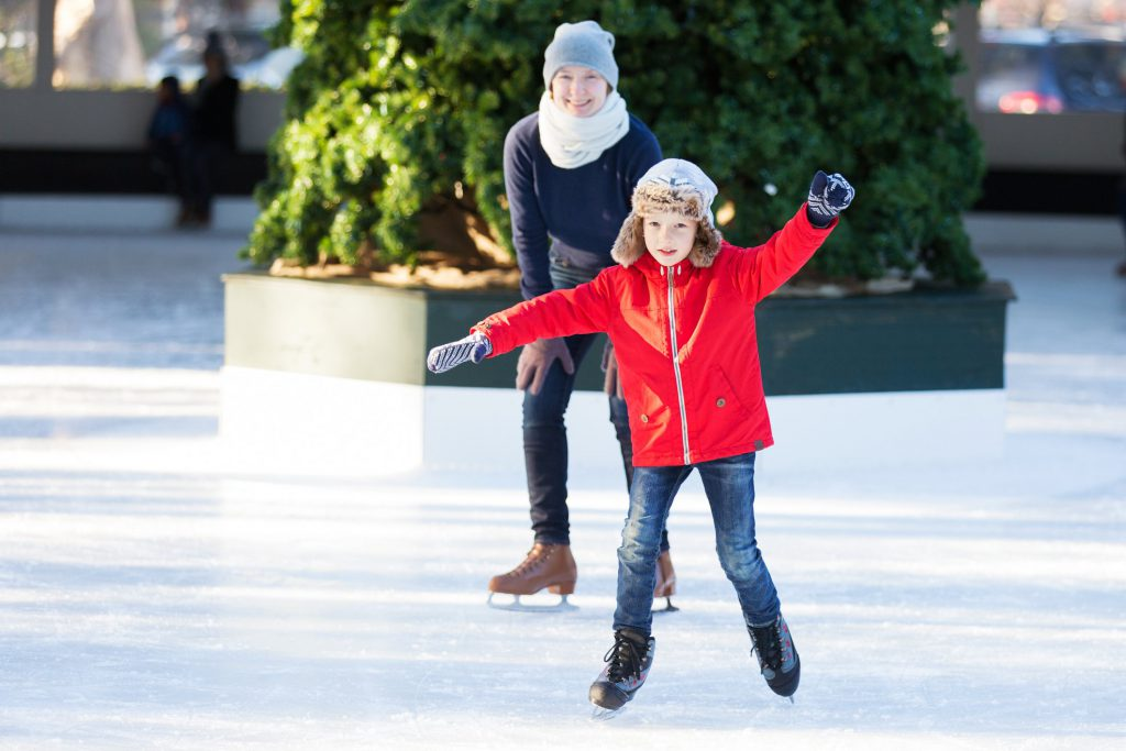A little girl ice skates with her mother on an outdoor rink in San Francisco