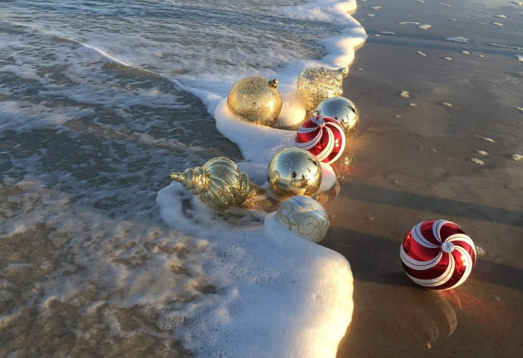 Gold and red and white striped Christmas ornaments float in the waves on Myrtle Beach