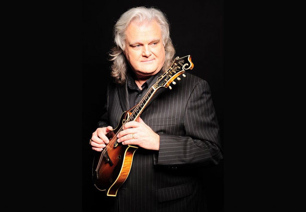 Ricky Skaggs holds a Mandolin while wearing a black pin-striped suit.