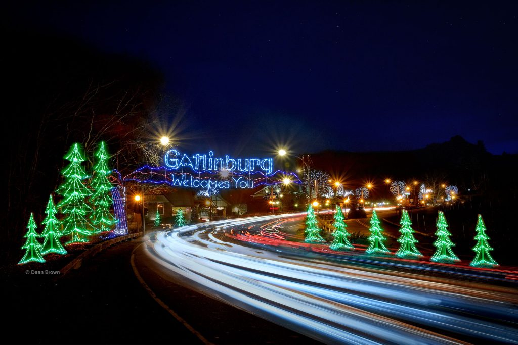 "Christmas light decorations shaped like trees line the roadway, along with a sign saying ""Gatlinburg Welcomes You."""