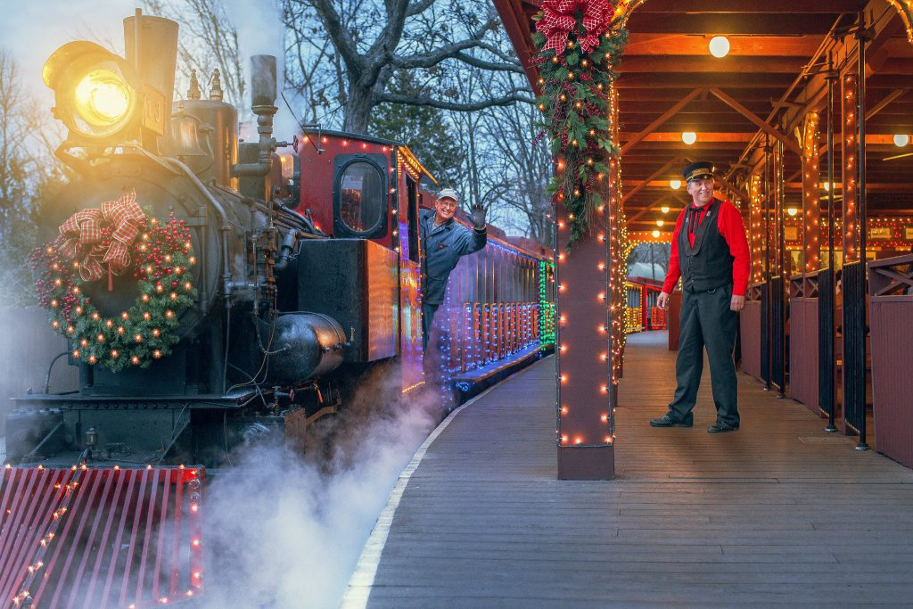 A train decorated with a Christmas wreath and lights pulls up to a train station modeled after the 1880s era.