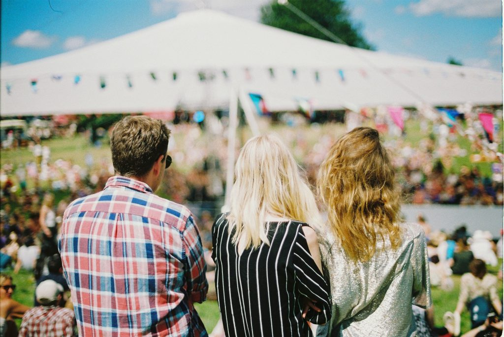 Three friends sit down at an outdoor festival
