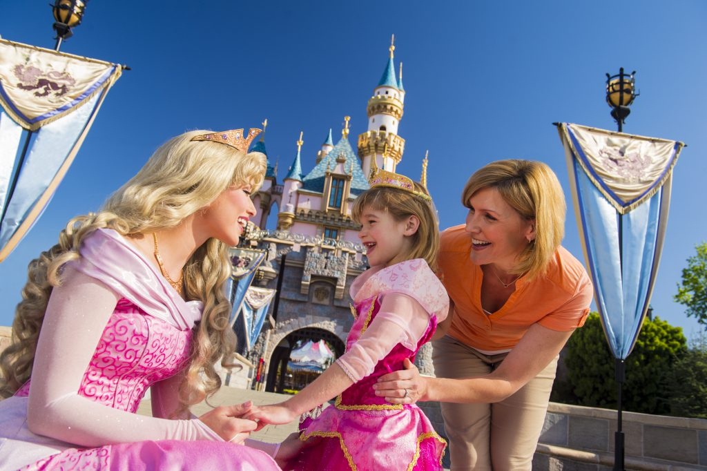 A little girl dressed up as Sleeping Beauty meets Sleeping Beauty outside of the Castle with her mom in Disneyland