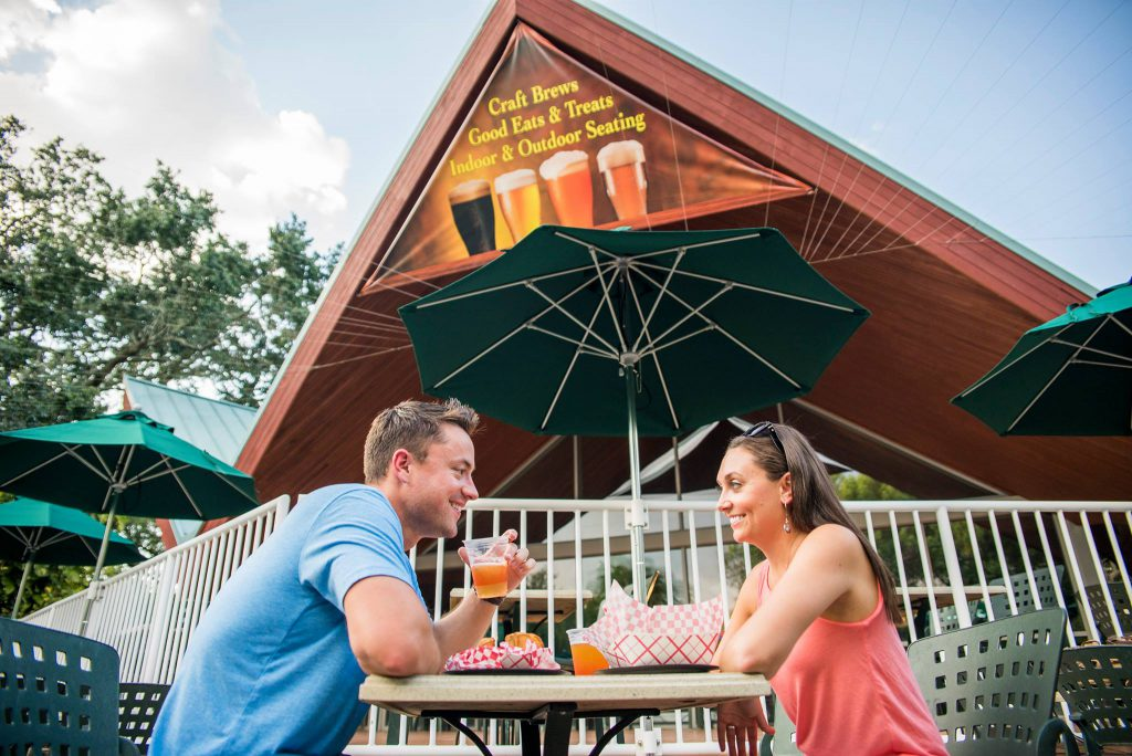 A man in a blue shirt and a girl in a pink tank top enjoy beer & food at Busch Gardens Tampa's Bier Fest