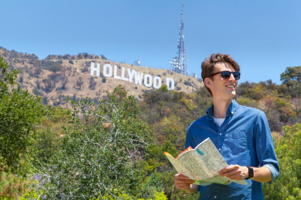 A young man in a blue button up shirt and black sunglasses holds a map. The Hollywood sign on the mountain is in the distance.