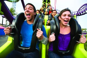A man and a woman ride a green and purple roller coaster at Knott's Berry Farm in Los Angeles