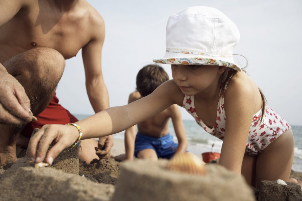 A little girl wearing a beach hat and bathing suit builds a sandcastle with her father
