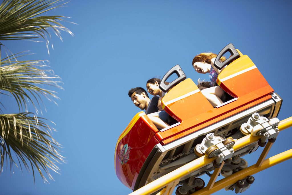A family rides an orange roller coaster at one of the Los Angeles area theme parks