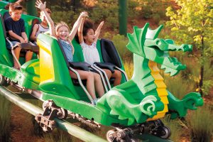 Two young girls ride a green dragon shaped rollercoaster at LEGOLAND California