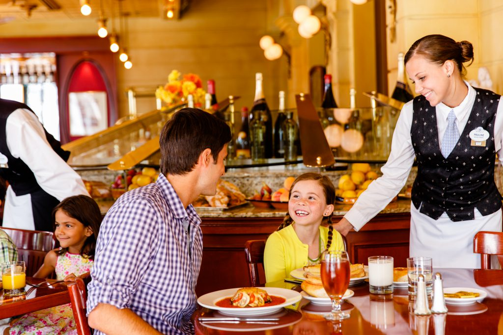 Father and daughter dining at a Disney World restaurant - Benefits of Staying on Disney Property