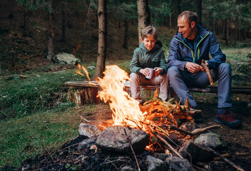 Gatlinburg Packing List: Father and Son drinking from mugs around a campfire.