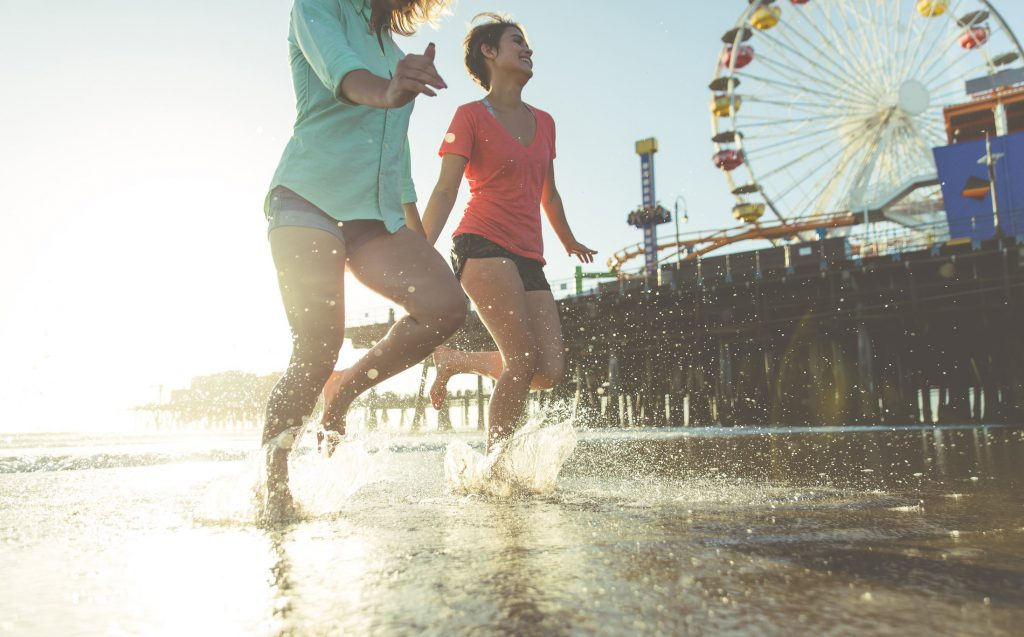 Two girls running in the ocean with the Santa Monica Pier in the background