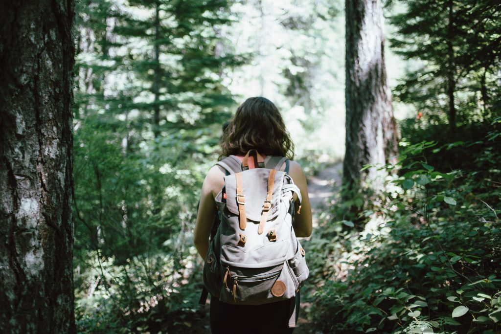 Girl hiking in the woods. Before packing, make sure you know what to bring to Williamsburg.