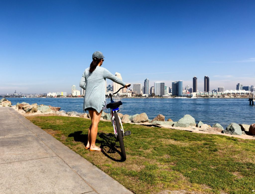 Woman bicycling overlooking San Diego skyline - what to pack for San Diego