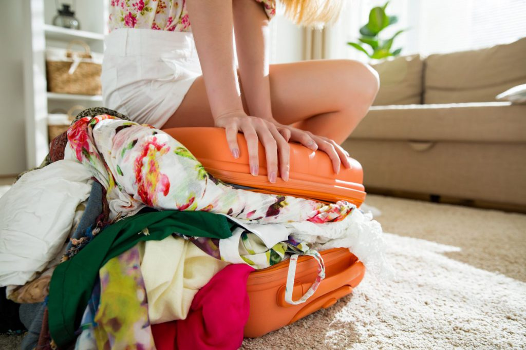 Know what to pack for San Diego - woman overpacking suitcase