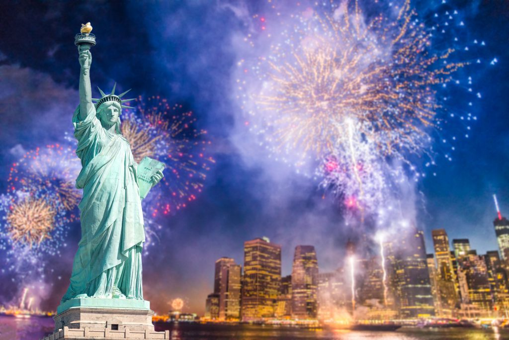 NYC 4th of July fireworks over the Statue of Liberty with a blurred NYC skyline background at night