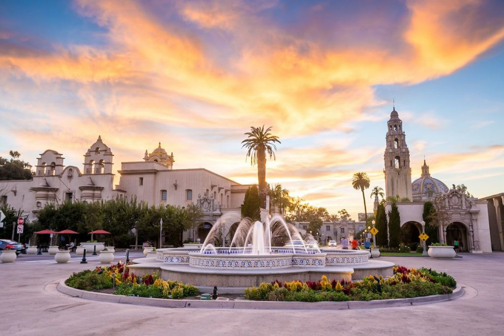Balboa Park at sunset with water fountain feature surrounded by museums and palm trees
