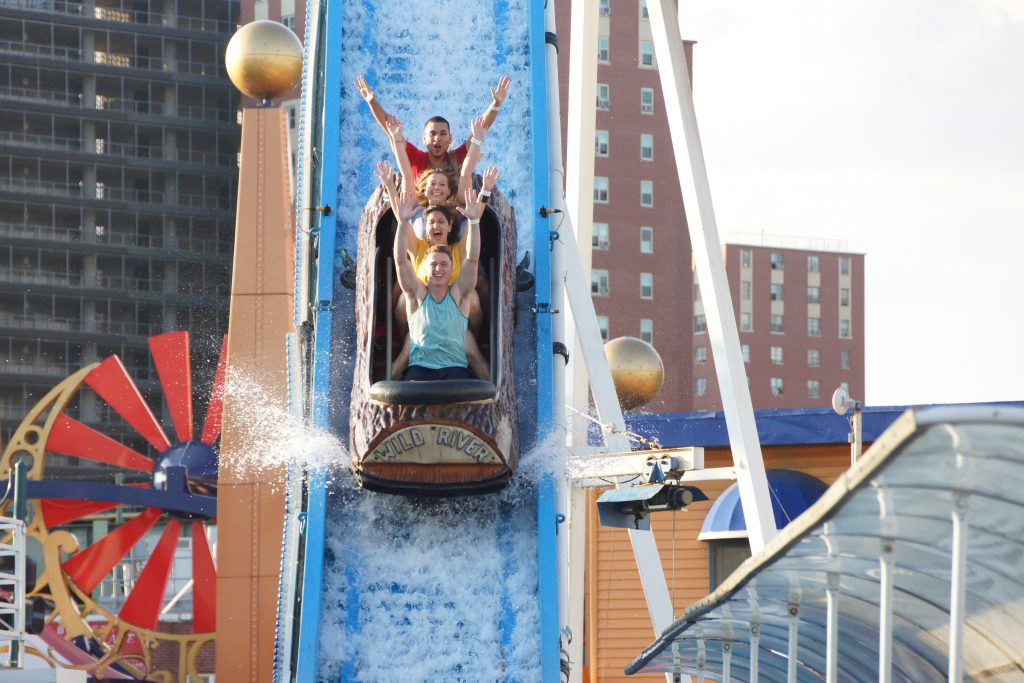 Group of friends plunge down a log flume ride at Luna Park in NYC, one of the best things to do in NYC in the summer.