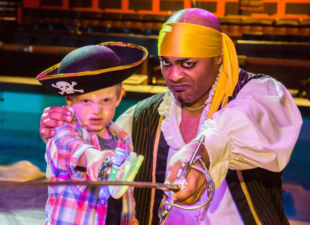 A kid wearing pirate attire points a sword at the camera with another pirate