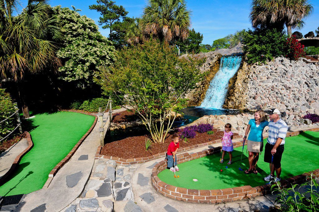 Family mini-golfing on a course in Myrtle Beach, SC