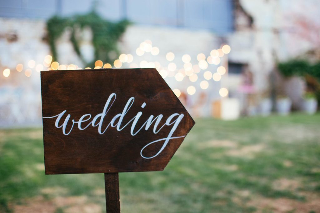 """Wooden sign with """"wedding"""" written in script pointing to the right"""