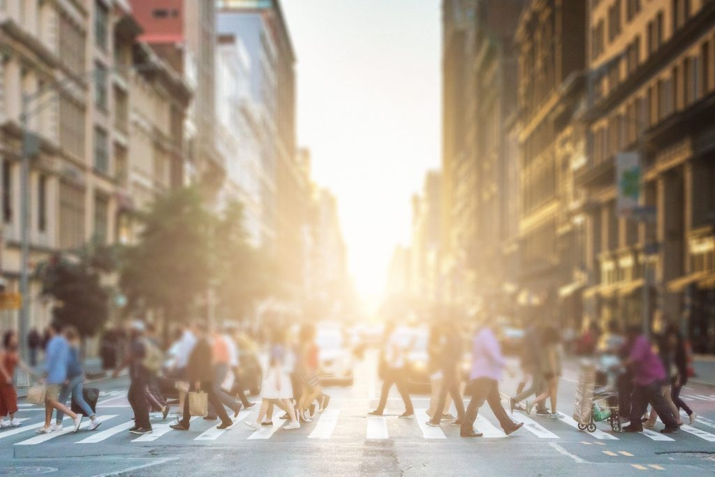 Group of pedestrians walking across an NYC street sidewalk as the sun sets in the summer.