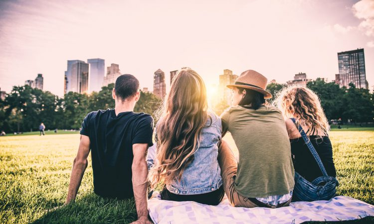 Friends enjoying the summer in Central Park overlooking the NYC skyline - 12 of the Best Things to Do in NYC in the Summer