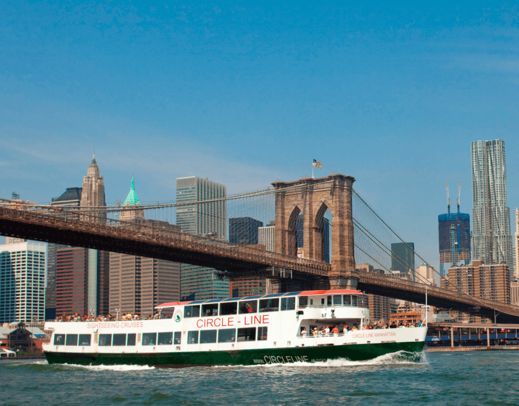 Tourists sail under the Brooklyn Bridge on a Circle Line Sightseeing Cruise ship.