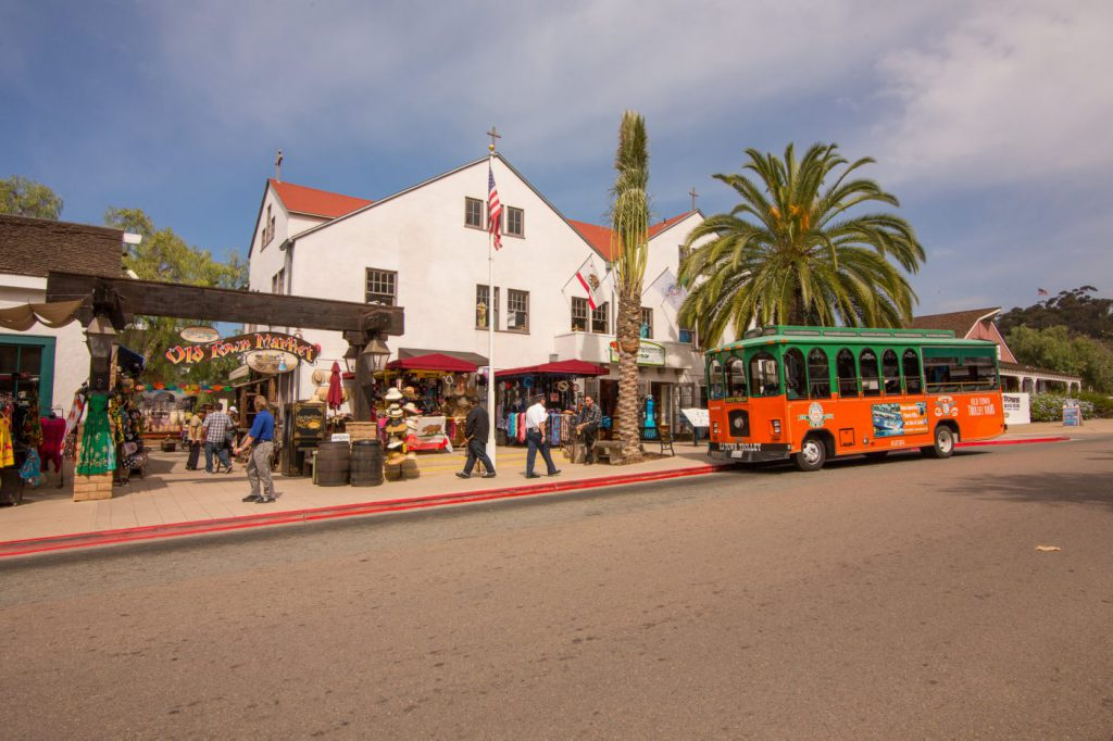 Orange and green Old Town Trolley outside of Old Town Market in San Diego