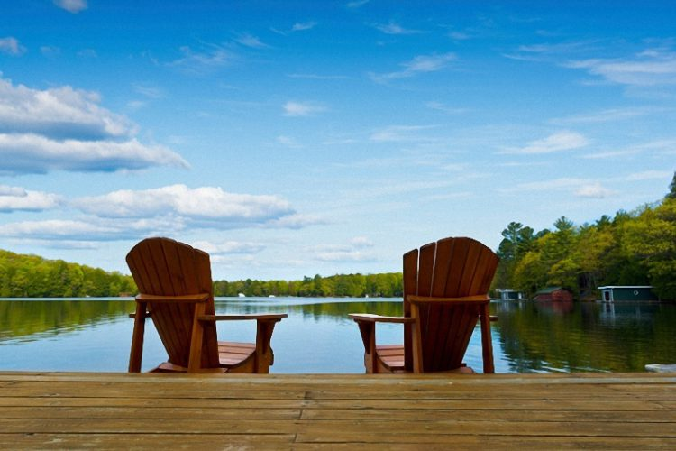 Two lake chairs facing the water on a sunny day