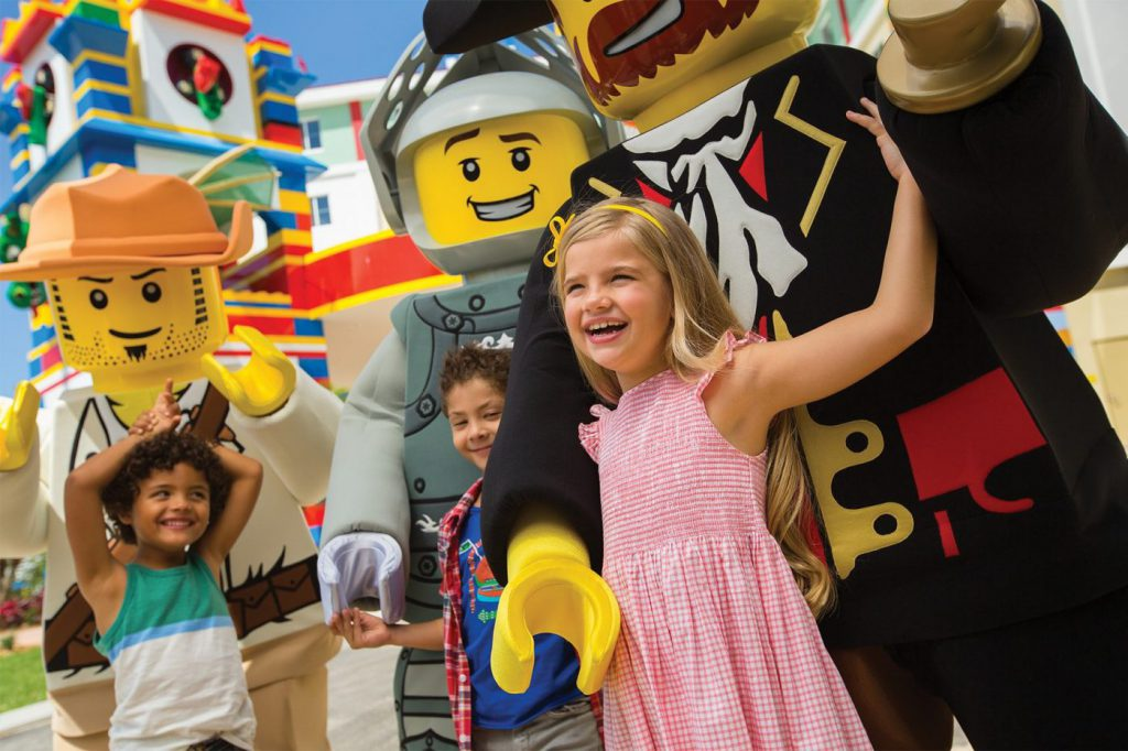 Little children standing next to costumed mini-figure characters at LEGOLAND California