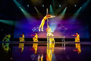 Amazing Acrobats of Shanghai perform feats of agility in yellow costumes