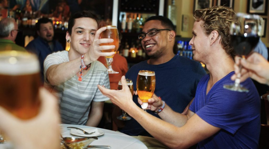 Tourists clink beer glasses together on a bar tour